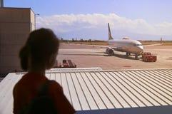 Muchacha adolescente que mira en la ventana del aeropuerto Imagen de archivo libre de regalías