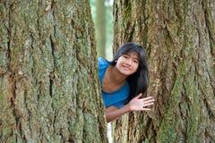 Muchacha adolescente que mira a escondidas con árboles, agitar y la sonrisa Imagen de archivo
