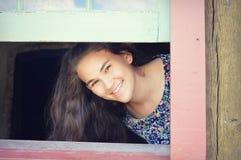 Muchacha adolescente que mira a escondidas a través de ventana Fotografía de archivo libre de regalías