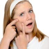 Muchacha adolescente que mira exprimir manchado piel de la espinilla Fotografía de archivo