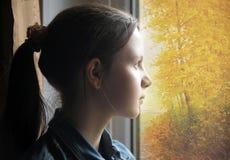 Muchacha adolescente que mira hacia fuera la ventana Fotos de archivo libres de regalías