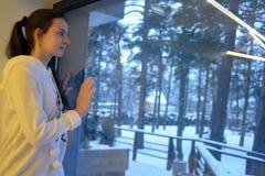 Muchacha adolescente que mira hacia fuera la ventana con un paisaje del invierno Fotos de archivo libres de regalías
