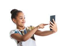 Muchacha adolescente que mira la pantalla de la tableta La muchacha de piel morena tiene señalar de la diversión Fotografía de archivo libre de regalías