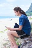 Muchacha adolescente que mira smartphone mientras que se sienta en la playa Fotografía de archivo