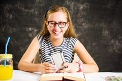 Muchacha adolescente que mira su teléfono y sonrisa Foto de archivo libre de regalías