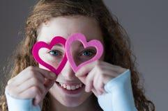 Muchacha adolescente que mira a través de corazones Imágenes de archivo libres de regalías