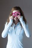 Muchacha adolescente que mira a través de corazones Imagen de archivo