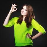 Muchacha adolescente que muestra gesto de mano aceptable de la muestra en negro Fotografía de archivo