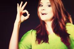 Muchacha adolescente que muestra gesto de mano aceptable de la muestra en negro Imágenes de archivo libres de regalías