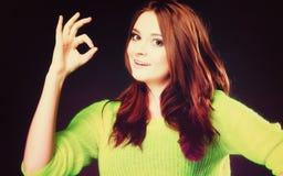 Muchacha adolescente que muestra gesto de mano aceptable de la muestra en negro Foto de archivo libre de regalías