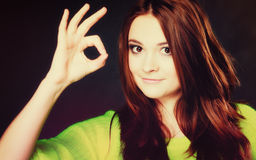 Muchacha adolescente que muestra gesto de mano aceptable de la muestra en negro Fotos de archivo