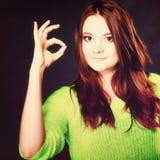 Muchacha adolescente que muestra gesto de mano aceptable de la muestra en negro Imagen de archivo