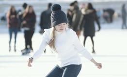 Muchacha adolescente que patina hábilmente en pista de hielo pública al aire libre Foto de archivo