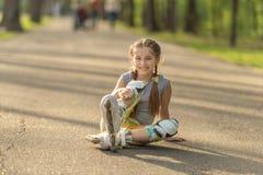 Muchacha adolescente que patina, sentándose en el asfalto y la reclinación Fotografía de archivo