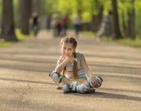 Muchacha adolescente que patina, sentándose en el asfalto y la reclinación Imagen de archivo libre de regalías