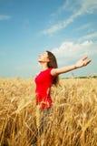Muchacha adolescente que permanece en un campo de trigo Imagen de archivo