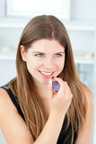Muchacha adolescente que pone el lápiz labial rojo Imagen de archivo
