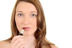 Muchacha adolescente que pone en el lápiz labial rojo Imágenes de archivo libres de regalías