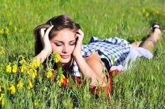 Muchacha adolescente que pone en el prado Fotos de archivo