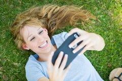 Muchacha adolescente que pone en la hierba que toma un Selfie con su Smart Foto de archivo libre de regalías