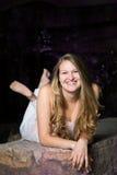 Muchacha adolescente que pone en roca Imagenes de archivo