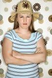 Muchacha adolescente que pone mala cara con los brazos cruzados. Foto de archivo libre de regalías