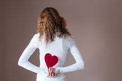 Muchacha adolescente que retiene corazones detrás de ella Imagenes de archivo