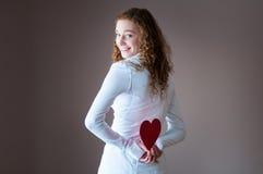 Muchacha adolescente que retiene corazones detrás de ella Imágenes de archivo libres de regalías