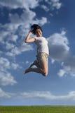 Muchacha adolescente que salta arriba en el cielo Fotografía de archivo