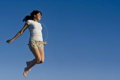 Muchacha adolescente que salta en el cielo Foto de archivo