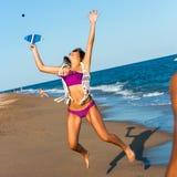 Muchacha adolescente que salta en la bola en la playa. Imágenes de archivo libres de regalías