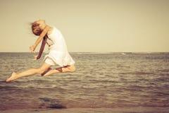 Muchacha adolescente que salta en la playa Foto de archivo