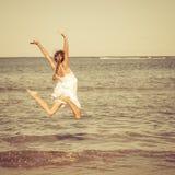 Muchacha adolescente que salta en la playa Imagen de archivo