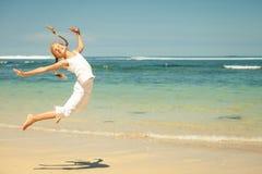 Muchacha adolescente que salta en la playa Fotos de archivo