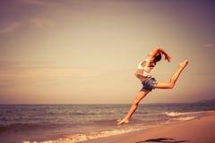 Muchacha adolescente que salta en la playa Fotografía de archivo