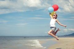 Muchacha adolescente que salta en la playa en el tiempo del día Foto de archivo