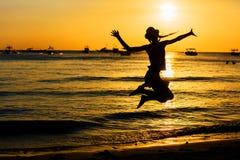 Muchacha adolescente que salta en la playa en el tiempo del día Foto de archivo libre de regalías