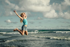 Muchacha adolescente que salta en la playa en la orilla de mar azul Fotografía de archivo