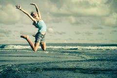 Muchacha adolescente que salta en la playa en la orilla de mar azul Fotografía de archivo libre de regalías