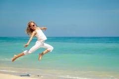 Muchacha adolescente que salta en la playa en la orilla de mar azul Fotos de archivo libres de regalías
