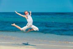 Muchacha adolescente que salta en la playa en la orilla de mar azul en vaca del verano Fotografía de archivo libre de regalías