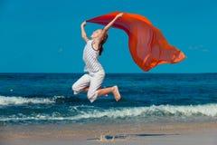 Muchacha adolescente que salta en la playa en la orilla de mar azul en vaca del verano Imagen de archivo libre de regalías