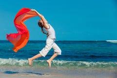 Muchacha adolescente que salta en la playa en la orilla de mar azul en vaca del verano Imágenes de archivo libres de regalías