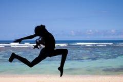 Muchacha adolescente que salta en la playa en la orilla de mar azul en vaca del verano Imagen de archivo