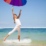 Muchacha adolescente que salta en la playa en la orilla de mar azul en vaca del verano Foto de archivo