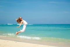 Muchacha adolescente que salta en la playa en la orilla de mar azul en vaca del verano Fotografía de archivo