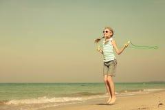 Muchacha adolescente que salta en la playa en la orilla de mar azul en vaca del verano Foto de archivo libre de regalías