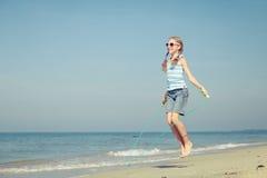 Muchacha adolescente que salta en la playa en la orilla de mar azul en vaca del verano Fotos de archivo libres de regalías