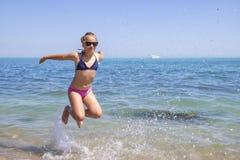 Muchacha adolescente que salta en la playa en la orilla de mar azul en vacaciones de verano en el tiempo del día Fotos de archivo libres de regalías