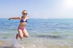 Muchacha adolescente que salta en la playa en la orilla de mar azul en vacaciones de verano en el tiempo del día Imagen de archivo